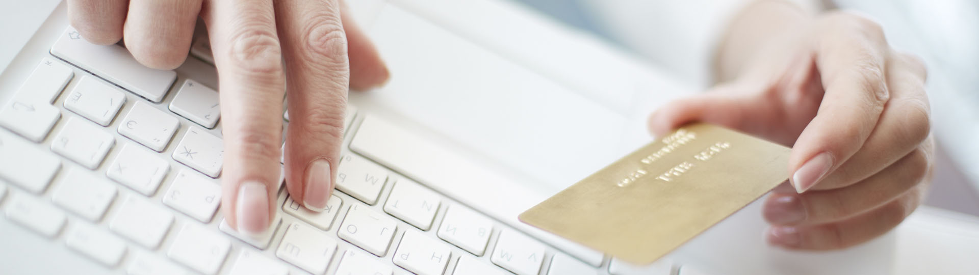 zoomed in image of a woman holding a credit card in one hand while pressing a keyboard button with the other